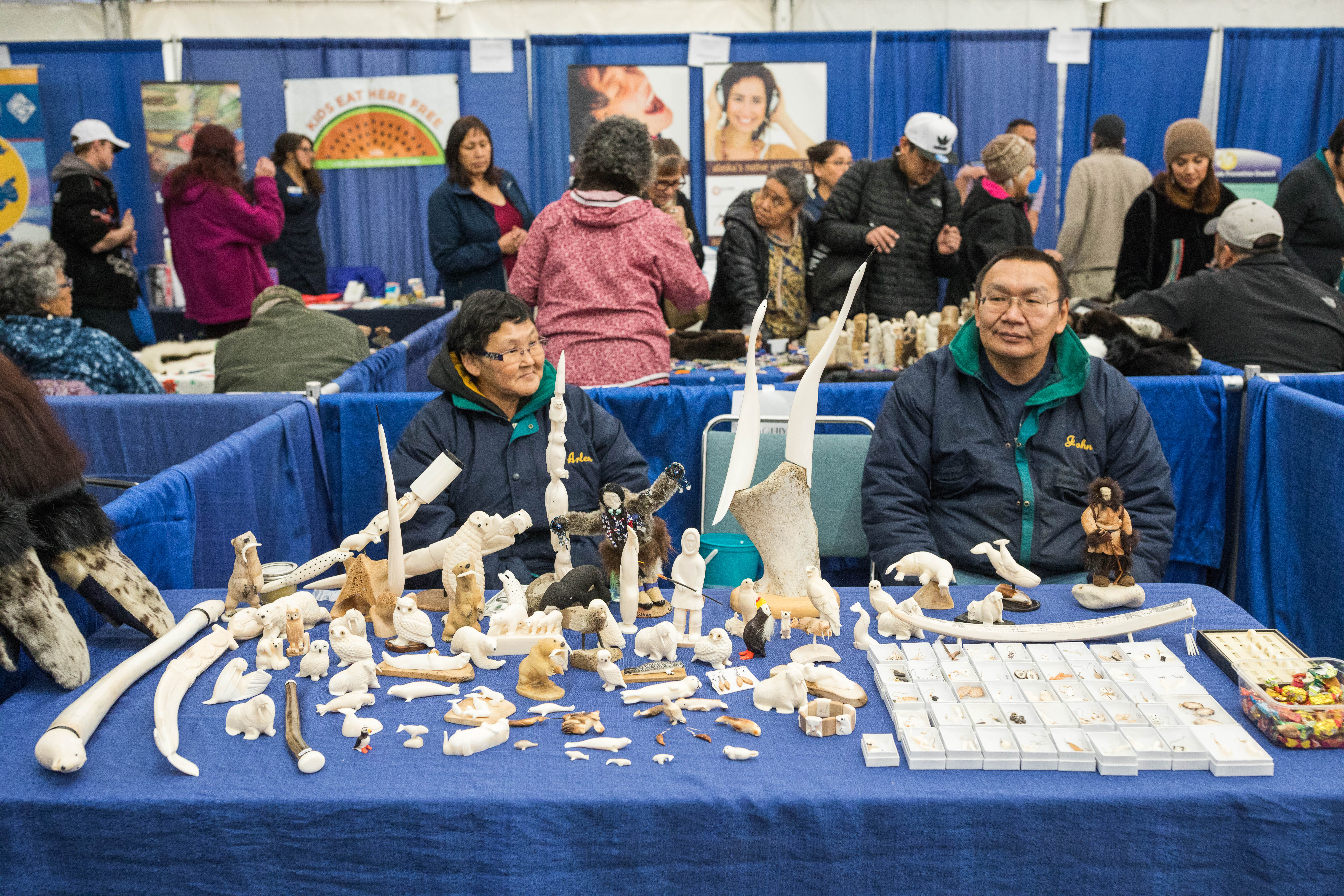 Arlene and John Waghiyi offer St. Lawrence Island walrus ivory carvings for sale in the arts and crafts tent at the Alaska Federation of Natives conference in Fairbanks on Thursday, Oct. 20, 2016. (Loren Holmes / Alaska Dispatch News)