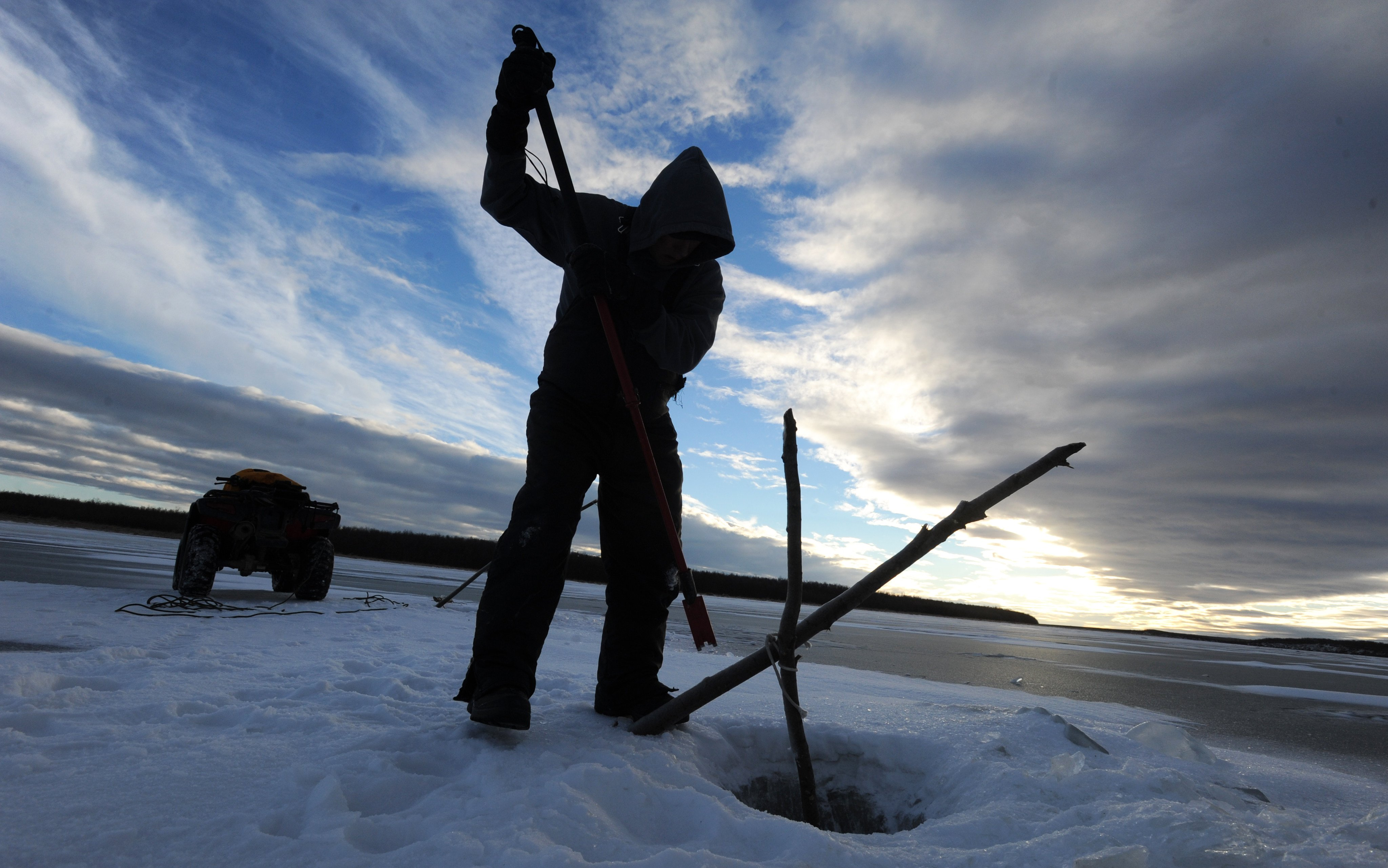 Richard Kammeyer of Bethel chips away ice on the frozen Kuskokwim River to check his subsistence gill net on Thursday, Jan. 8, 2015. Kammeyer was hoping to find whitefish, lush or burbot, sheefish, and even pike, but his net came up empty. (Bill Roth / Alaska Dispatch News)