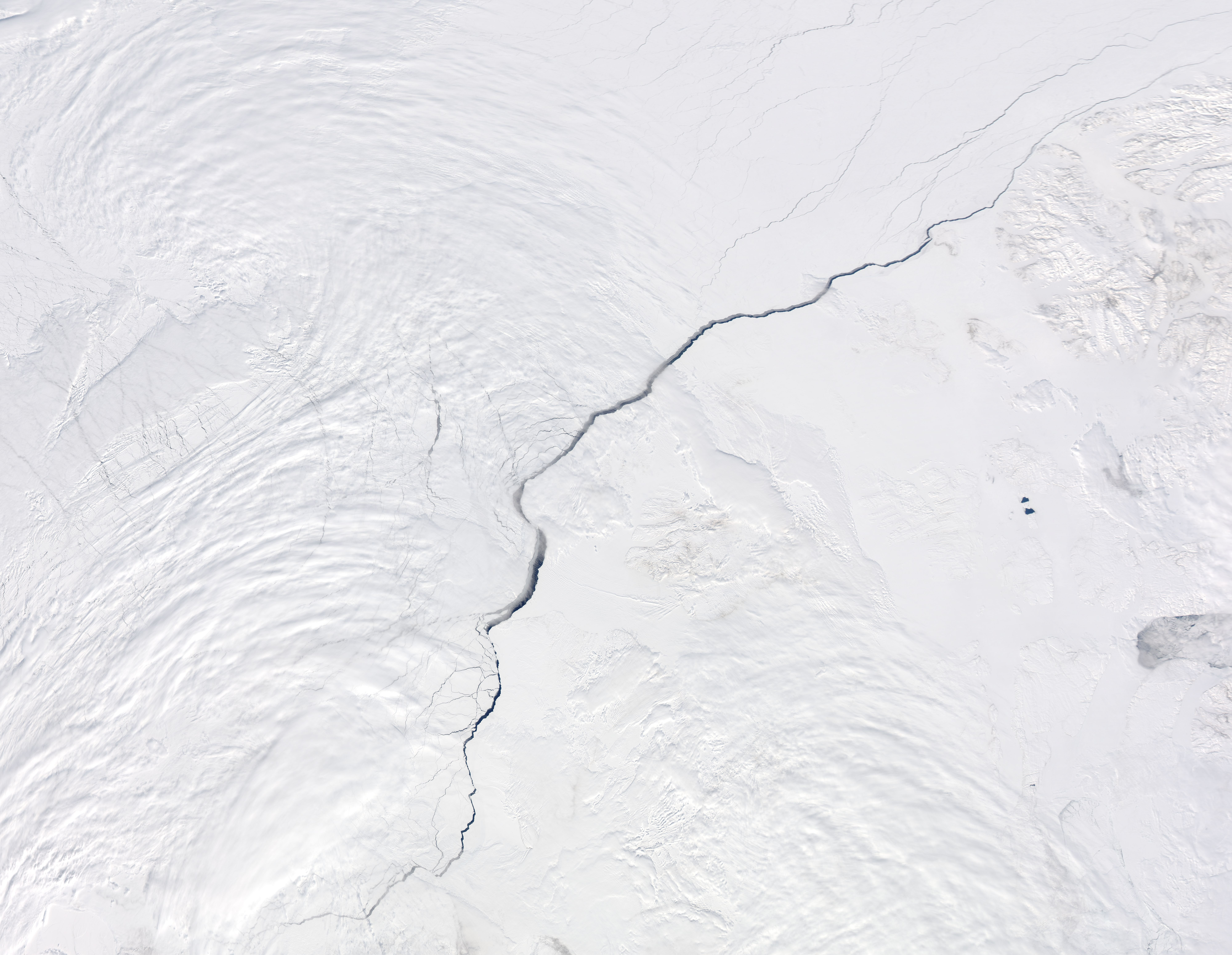 The Moderate Resolution Imaging Spectroradiometer (MODIS) aboard NASA's Aqua satellite captured this true-color image of a large open water lead traversing the ice of the northern Arctic Ocean on May 13, 2013. Located north of Canada, the long, wide crack extends hundreds of kilometers across the ice to end north of the Arctic Circle. (NASA/GSFC/Jeff Schmaltz/MODIS Land Rapid Response Team)