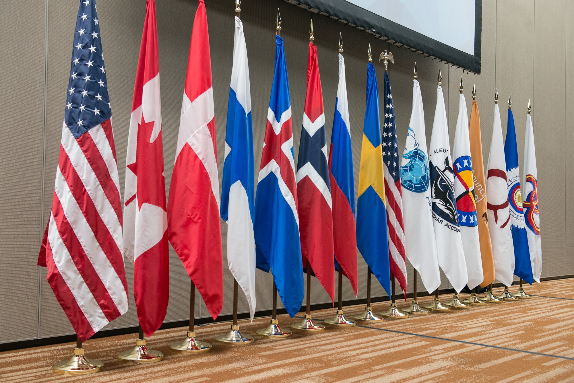 The flags of the eight Arctic Council Member States and six indigenous Permanent Participant organizations, at the first SAO meeting during the United States' 2015-2017 Chairmanship held in Anchorage, Alaska Oct. 20-22. (Arctic Council Secretariat / Linnea Nordström)