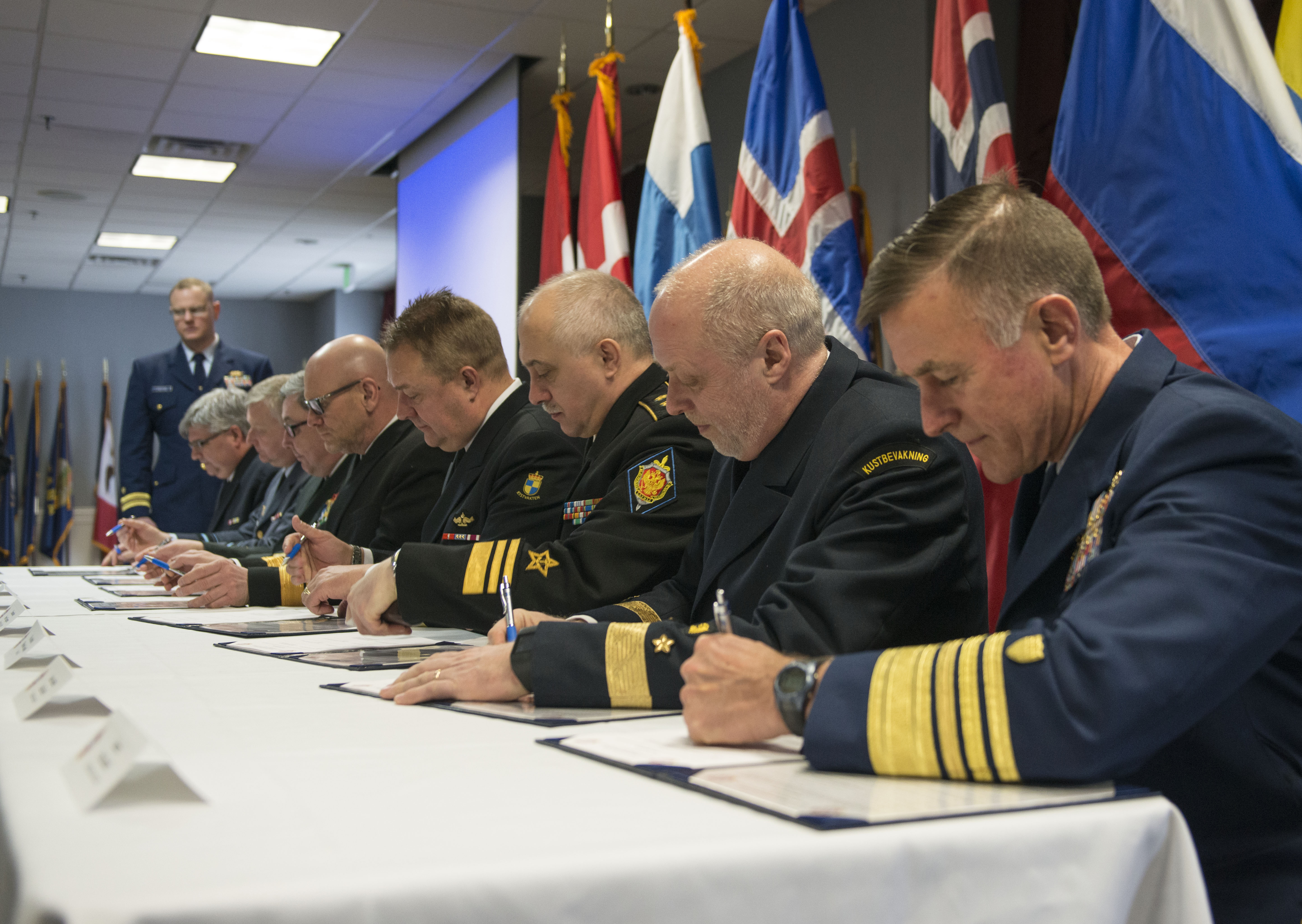 U.S. Coast Guard Commandant Adm. Paul Zukunft joins leaders representing eight coast guard agencies of Arctic nations in signing a joint statement in Boston, Friday, March 24, 2017. The statement adopts doctrine, tactics, procedures and information-sharing protocols for emergency maritime response and combined operations in the Arctic. (Petty Officer 2nd Class Cynthia Oldham / U.S. Coast Guard)