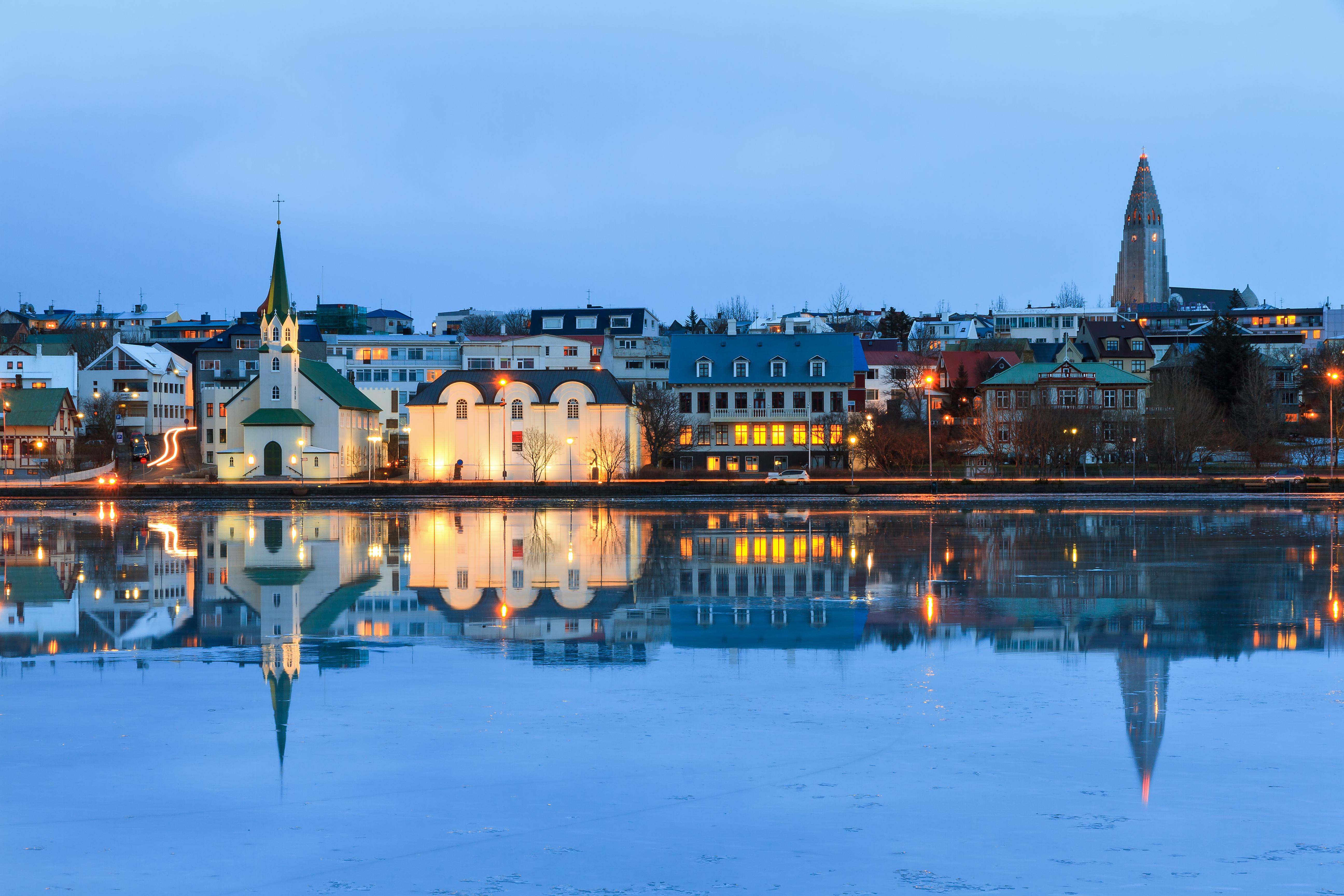 The cityscape of Reykjavik is reflected in lake Tjornin in winter. (Getty)