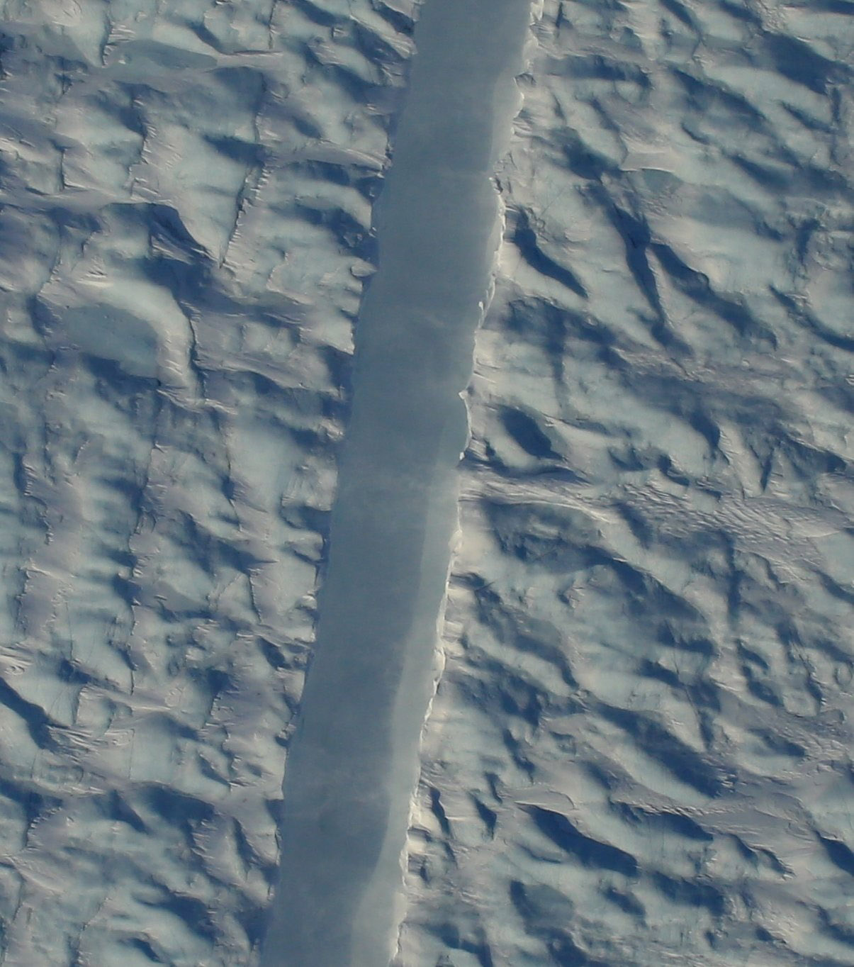 A preliminary image from NASA's Digital Mapping Service shows the new rift in Greenland's Petermann glacier, directly beneath the NASA Operation Icebridge aircraft. (NASA DMS photo by Gary Hoffmann)