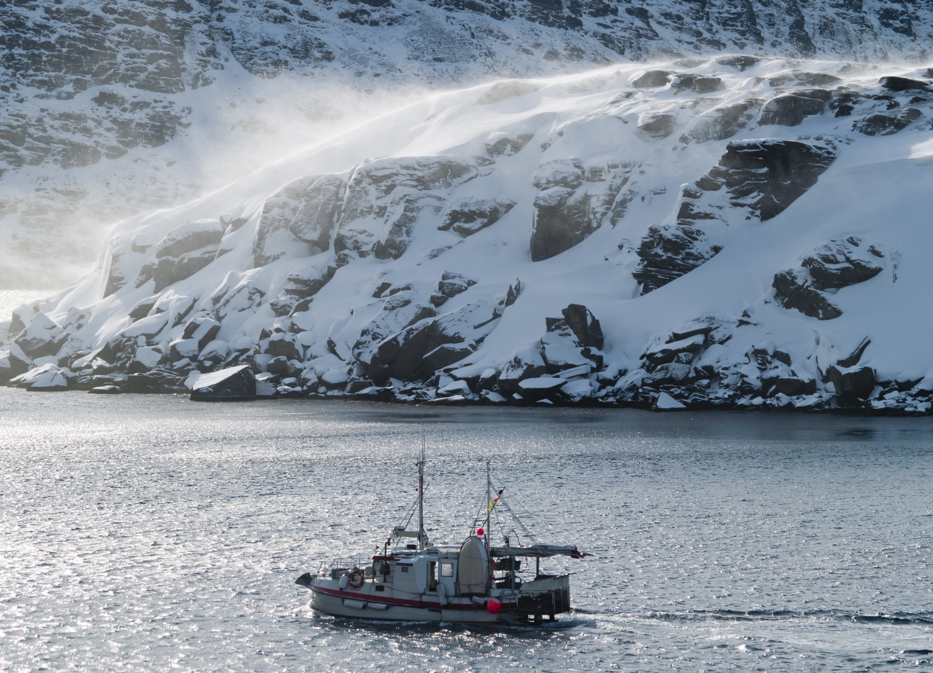 Fishing boat on the Barents Sea in Norway's Arctic region in winter. Blowing snow on the rocky headland behind. (Getty)