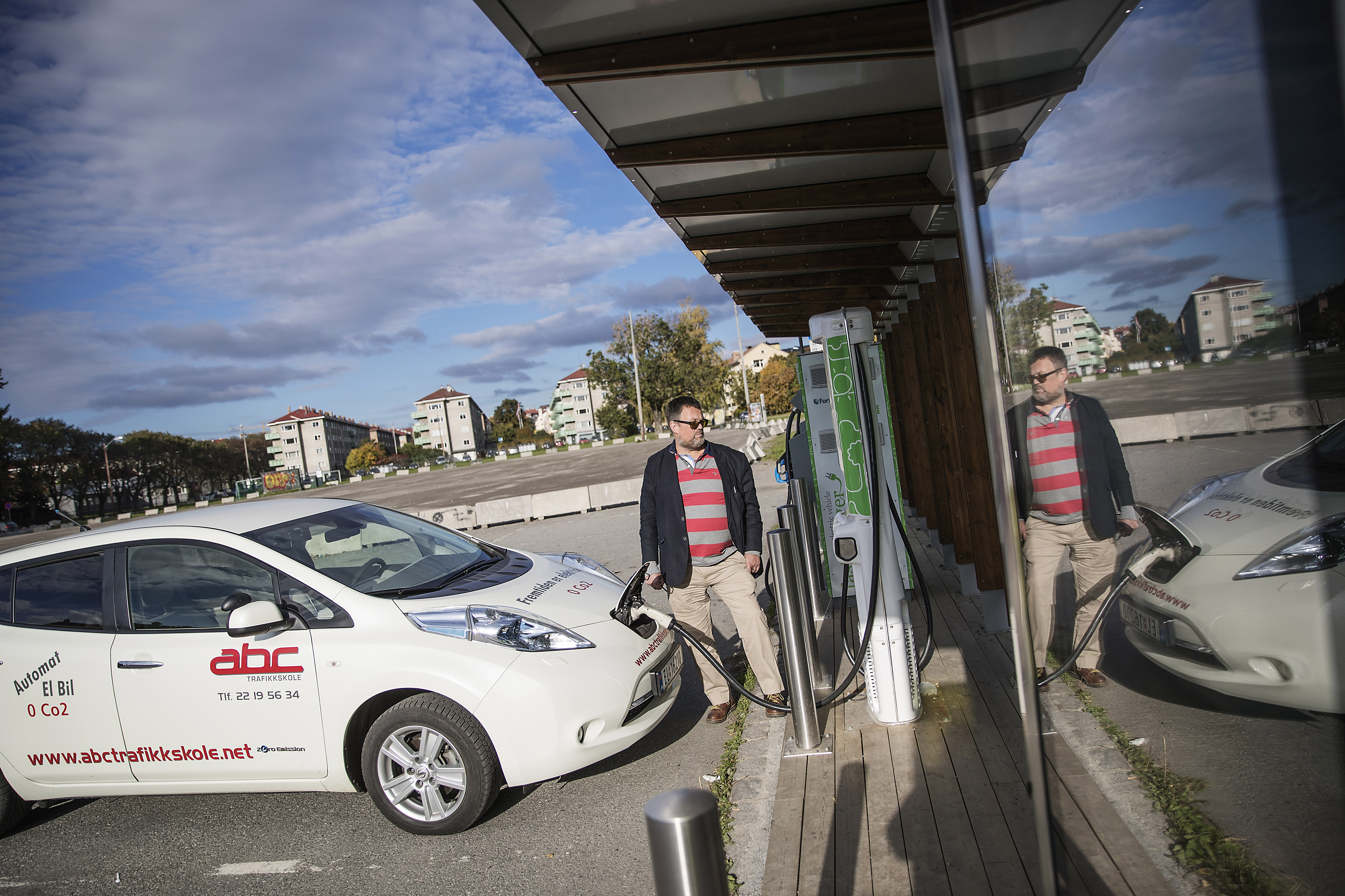 A driving-school owner charges an electric Nissan Leaf near his office in Oslo, Norway, Oct. 10, 2016. While Norway offers major breaks to electric car owners in a bid to wean its own citizens off fossil fuels, it remains one of the world's biggest oil producers and is revving up production for exports, a contradiction not lost on critics. (Thomas Haugersveen/The New York Times)