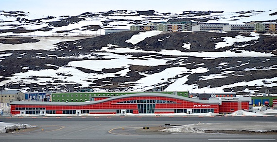 The shallow curved roof of the new Iqaluit air terminal, as seen from across the runway, is engineered to prevent snowdrift accumulation. Tall windows facing south let natural light shine deep into the terminal. The terminal's red colour, in keeping with the colours of other buildings in the city, makes it stand out. (Steve Ducharme / Nunatsiaq News)