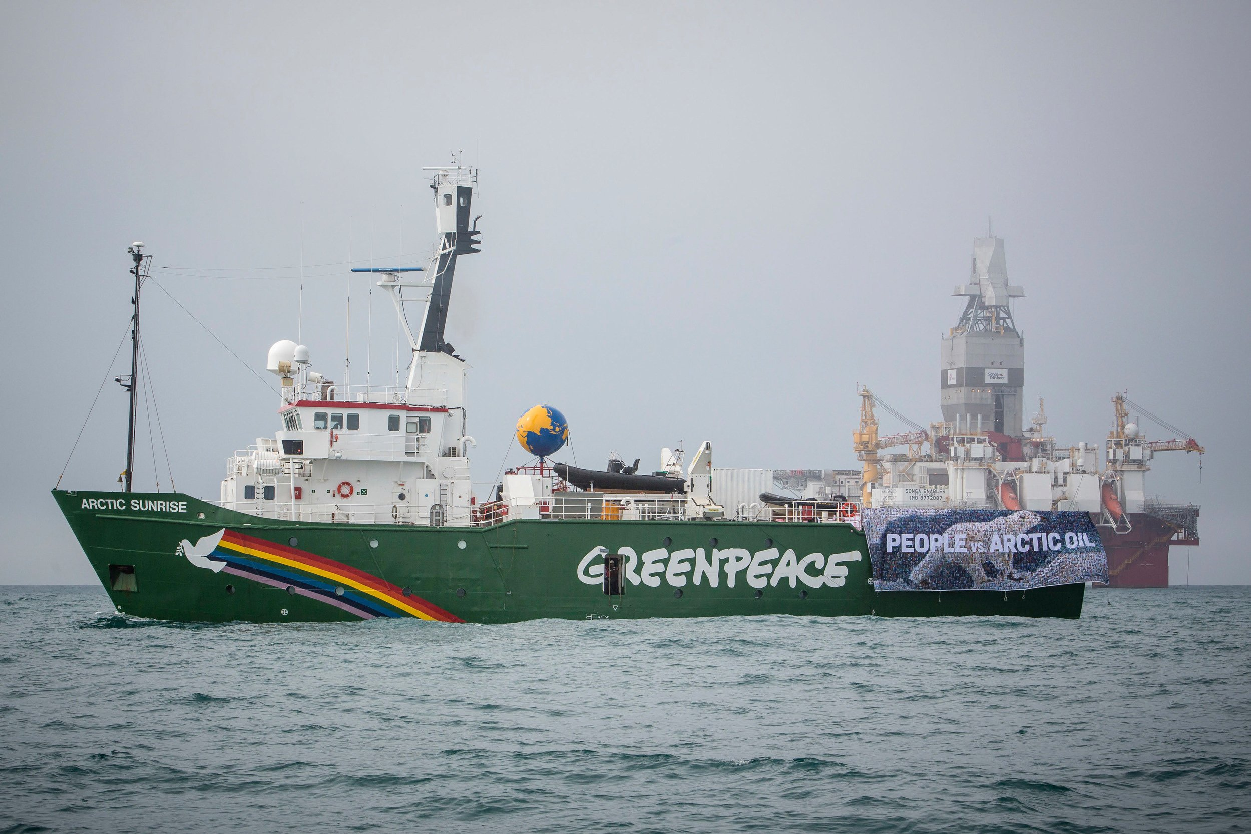 "Greenpeace's Arctic Sunrise vessel displays a banner reading ""People vs. Arctic Oil"" as it sails during a protest next to Statoil's Songa Enabler rig in the Barents sea, Norway, July 21, 2017. (Will Rose/ Greenpeace / Handout via Reuters)"