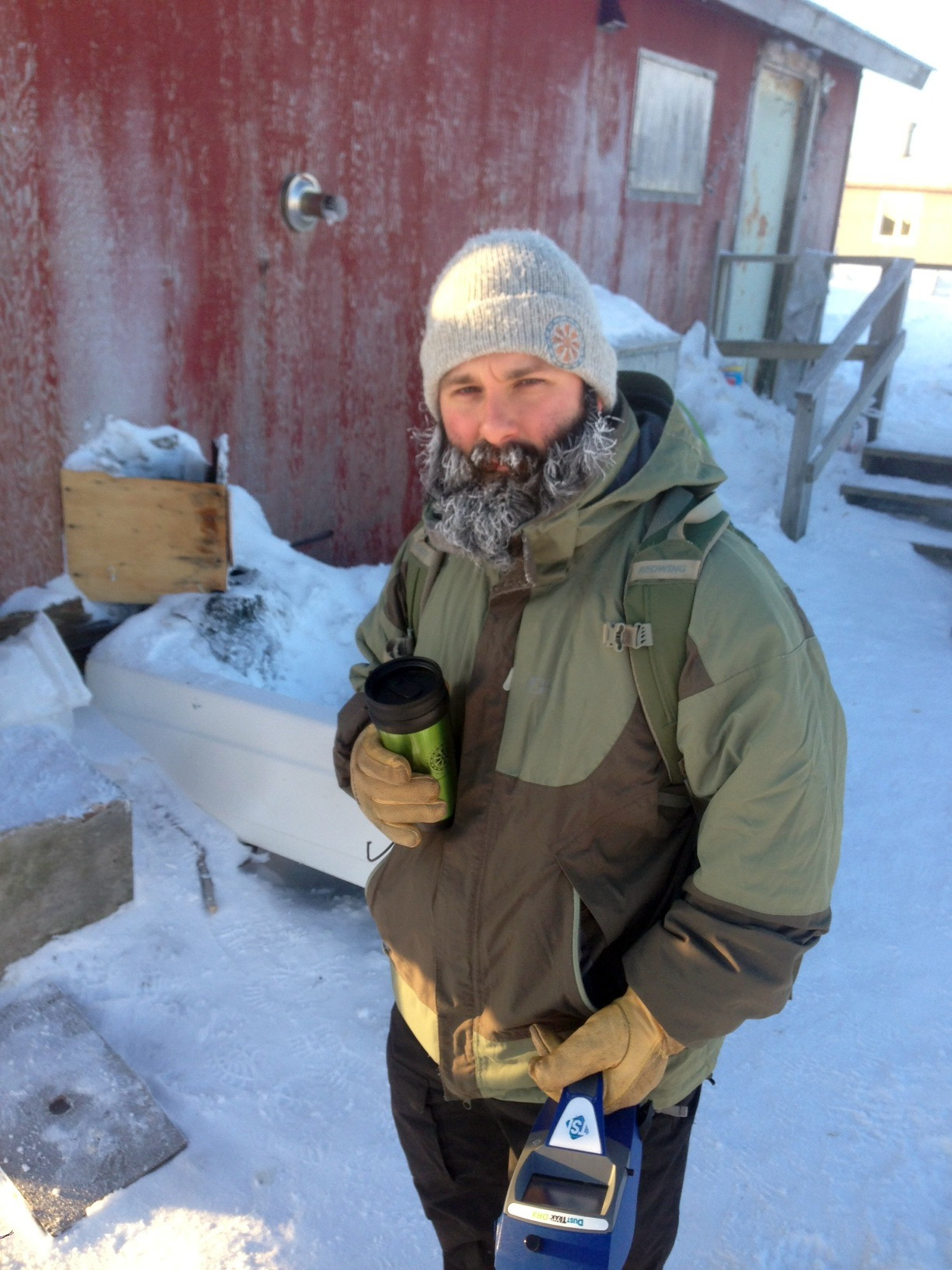 AJ Salkoski holds an air monitor outside a home in southwest Alaska during the winter of 2013. Salkoski is a Senior Program Manager at Alaska Native Tribal Health Consortium. He led a team to eight villages in southwest Alaska to conduct air quality tests and home improvements. (Courtesy AJ Salkoski / ANTHC)