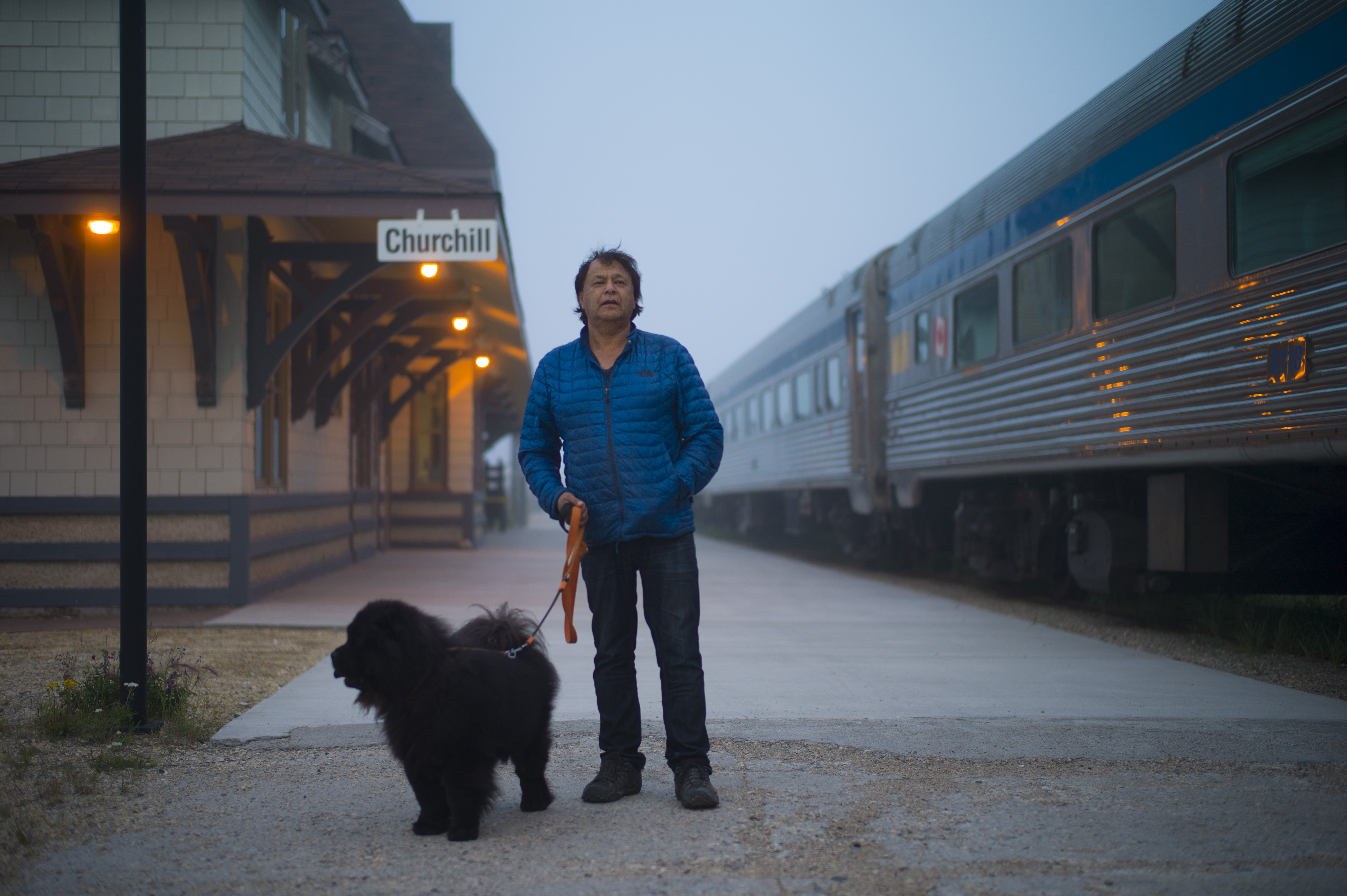Mayor Mike Spence and his dog at the now-disused train station in Churchill, Manitoba, Canada, July 25, 2017. Spence had expected this year to be Churchill's best summer tourist season because of discounted rail passes celebrating Canada's 150th birthday; instead the closure of the vital rail link due to washed-out bridges has dealt a possibly crippling economic blow. (Ian Willms / The New York Times)