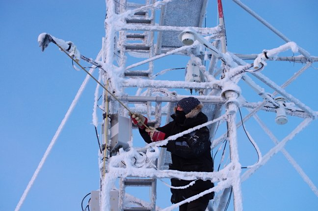 PEARL operator Peter McGovern cleans frost from instruments on a 10-metre-high flux tower. The tower measures properties in the atmosphere. (Pierre Fogal / Polar Environment Atmospheric Research Laboratory via Nunatsiaq News)