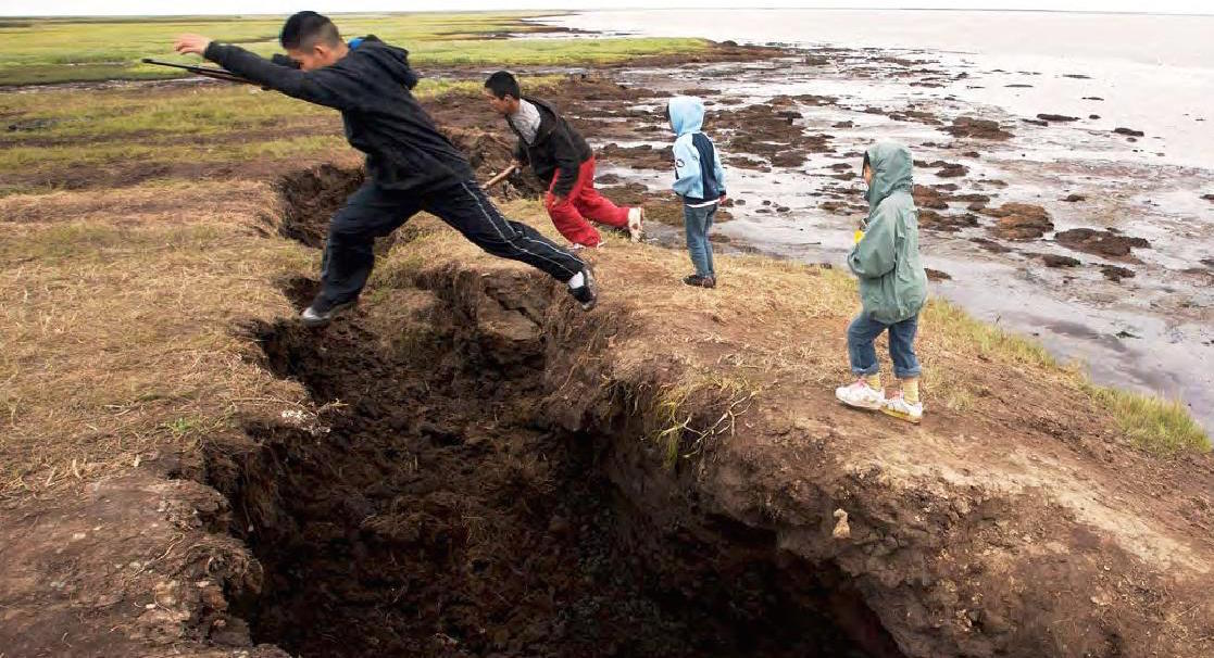 Children in Alaska jump across a crevasse created by coastal erosion. As sea ice fails to form and permafrost thaws, Arctic coasts are increasingly susceptible to the waves caused by storms. (NOAA)