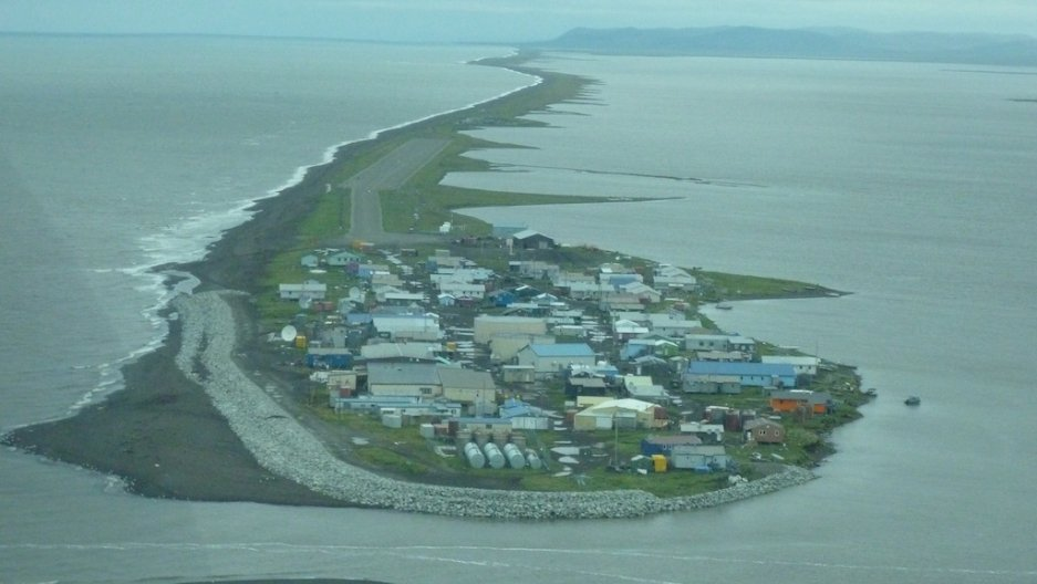 A gravel seawall (grey area at left) has already been built to protect Kivalina, Alaska, but keeping its people safe in the short term will require building a road to higher ground on the mainland (right, rear) (Relocate Kivalina)
