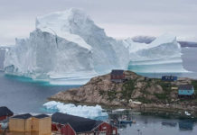 A huge iceberg has drifted close to a Greenland village, causing fears of a tsunami